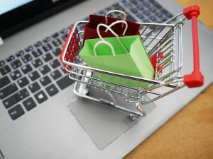 Tiny shopping cart with two presents resting on a laptop keyboard