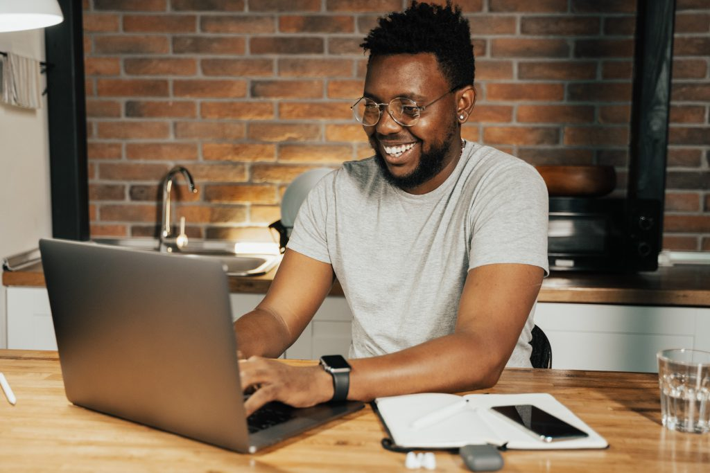 man working at computer, smiling