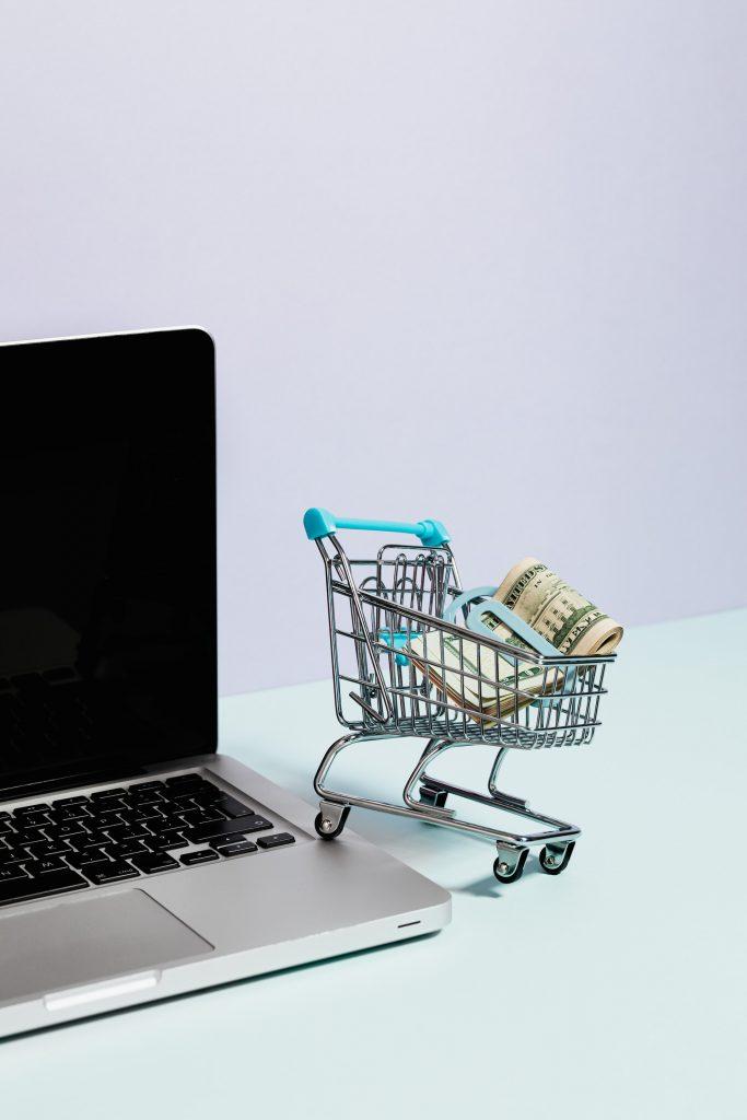 tiny cart of cash next to computer